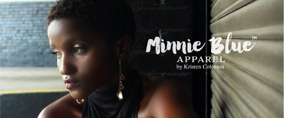 Model standing against a garage door wearing a black dress and dangling earrings. The words Minnie Blue Apparel by Kristen Colemon appear in logo format on the right side of the picture.