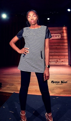 Model wearing a long white and black striped shirt with black sleeves and a pocket in the front and black jeggings. She is posing at the end of the runway.