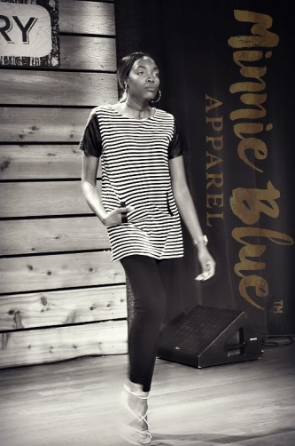 Black and white image of a model wearing a long white and black striped shirt with black sleeves and a pocket in the front and black jeggings. She is walking down the runway.