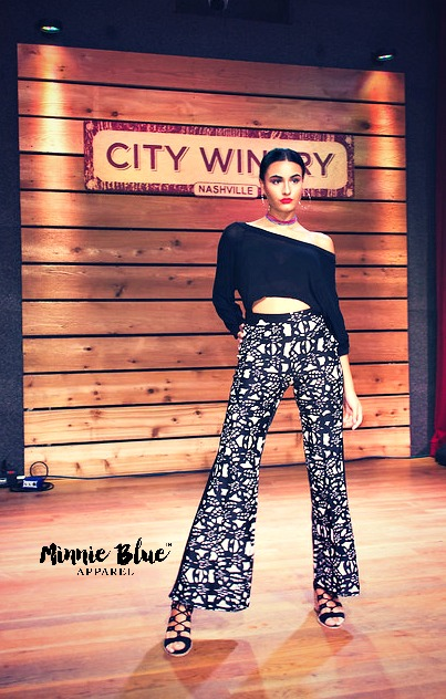 Black and white image of a model wearing a long sleeved black crop top with black and white patterned pants. She is posing on the runway.