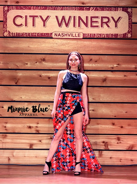 Model wearing a black crop with a long red, blue, cream and black patterned skirt with a slit on the left revealing a black shorts. She is posing on the runway.