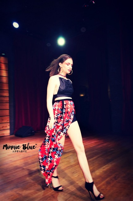 Model wearing a black crop with a long red, blue, cream and black patterned skirt with a slit on the left revealing a black shorts. She is walking down the runway.