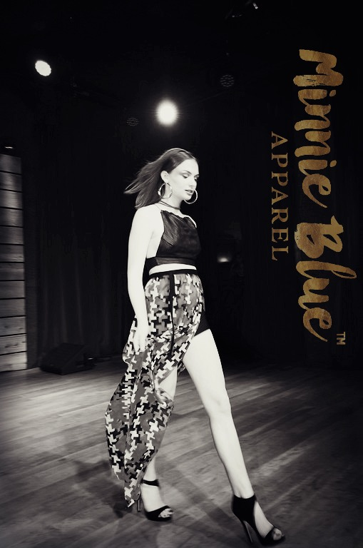 "Black and white image of a model wearing a black crop with a long red, blue, cream and black patterned skirt with a slit on the left revealing a black shorts. She is posing on the runway. The words ""minnie blue apparel"" are written in gold and positioned vertically along the right edge of the image."