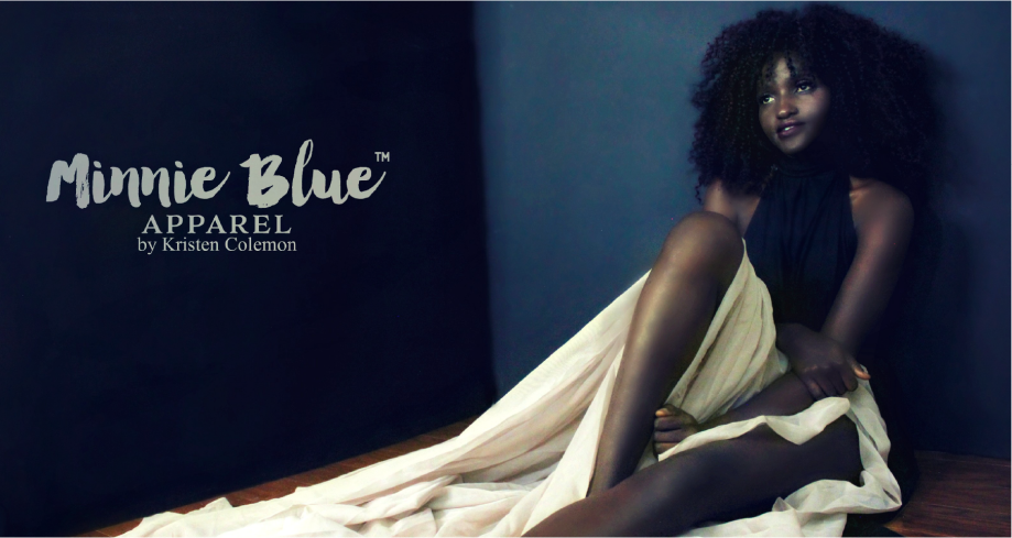 Model sitting on wooden floor leaning against a dark blueish gray wall wearing a long black and white gown. The words Minnie Blue Apparel by Kristen Colemon appear in logo format on the left side of the picture.