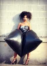 Model standing against cinder block wall wearing trash bag dress and heels.