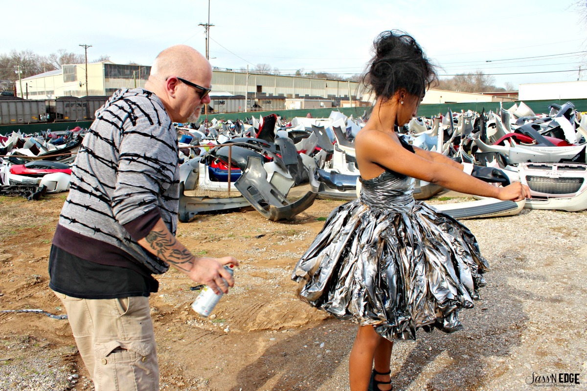 McNally spraying a model's trashbag dress on site of a trash collection shoot.