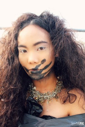 Headshot of a model at the trashback suit. She is wearing a crop top, saftey pin necklace and has a black handprint over her mouth.