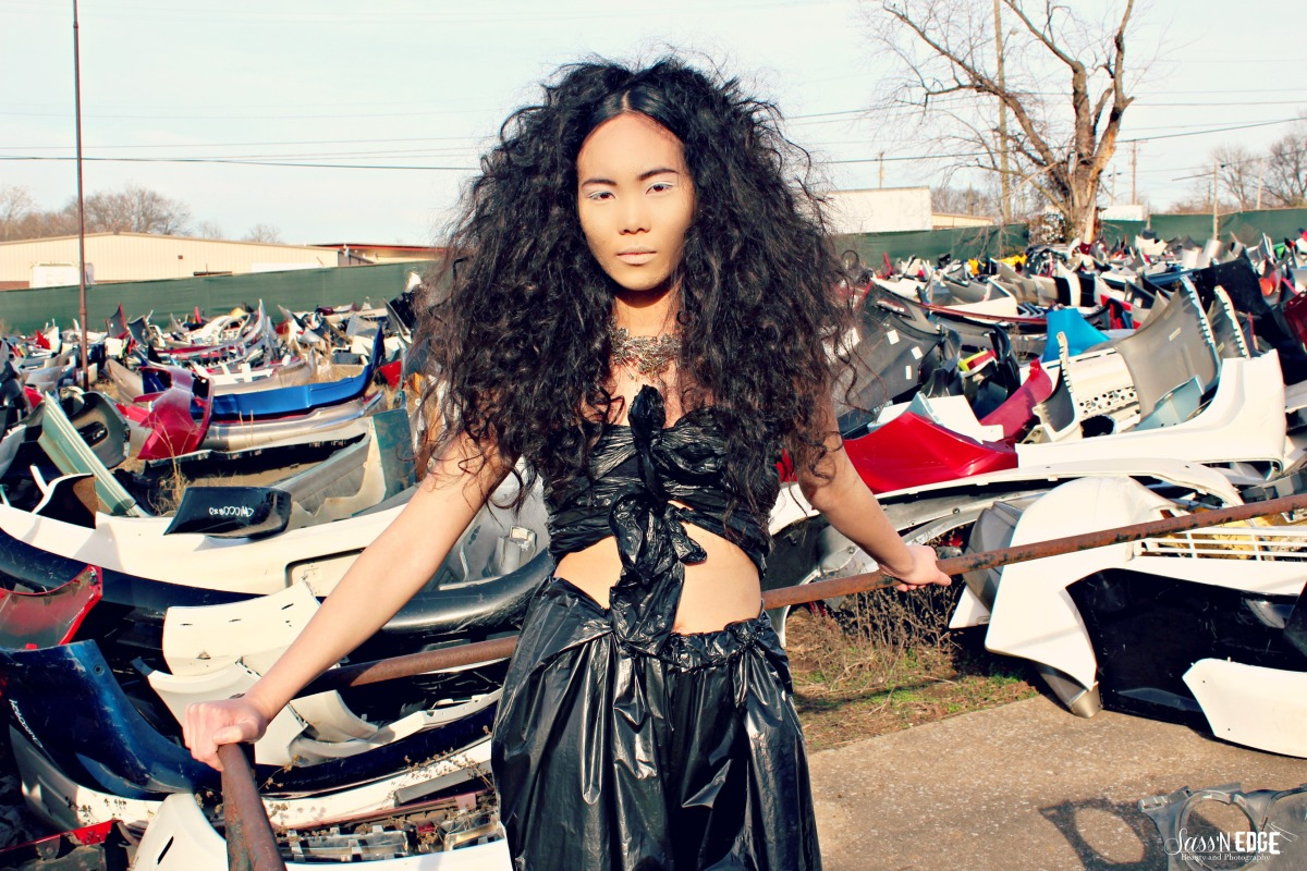 Model posing in a auto dump wearing a crop top and pants made of trash bags.
